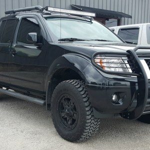 2016 Nissan Frontier PRO-4X with Westin grille guard, Rock Star wheels, Retrax One MX bed cover, roof rack light bar