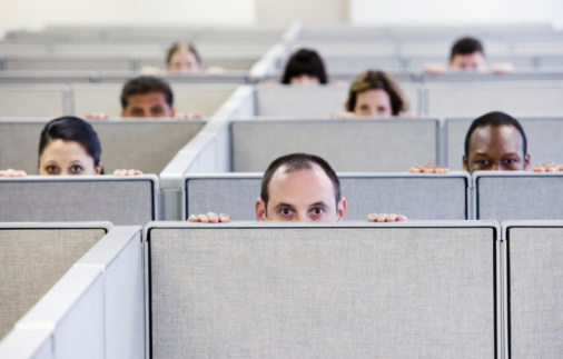 Office workers looking over cubicle wall, focus on foreground