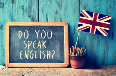 44292773 - a chalkboard with the text do you speak english? written in it, a pot with pencils and the flag of the united kingdom, on a wooden desk, with a filter effect