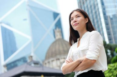 35126220 - business woman confident portrait in hong kong. businesswoman standing proud and successful in suit cross-armed. young multiracial chinese asian / caucasian female professional in central hong kong.