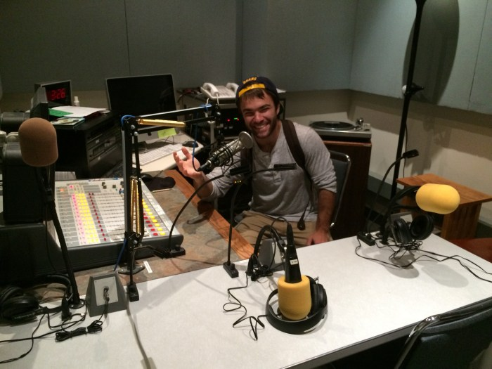 Rising sophomore David Straub, assistant director of sports, in the KALX studio sitting at the microphone  by Chelsea Siegal