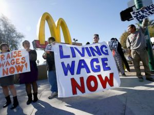 Citizens stand in protest of current minimum wage at the time in California in 2016. Photo by Ross D. Franklin, AP.