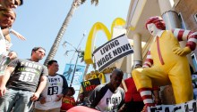 Robert Wideman, a maintenance mechanic at McDonalds Corp., shines the shoes of a Ronald McDonald statue outside of a restaurant while protesting with fast-food workers and supporters organized by the Service Employees International Union (SEIU)  on Thursday, Aug. 29, 2013. Photographer: Patrick T. Fallon/Bloomberg via Getty Images