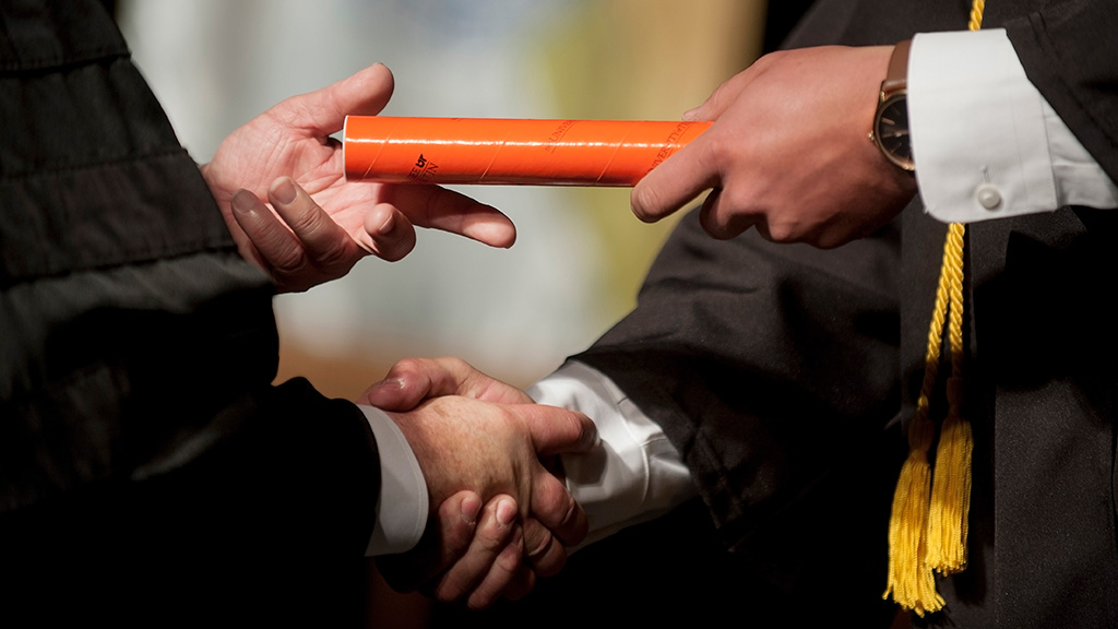 Close up of honor student shaking hands with college dean and recieving orange diploma tube