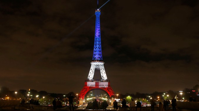 People look at the Eiffel Tower illuminated in the French colors in honor of the victims of the attacks on Friday in Paris, Monday, Nov. 16, 2015. France is urging its European partners to move swiftly to boost intelligence sharing, fight arms trafficking and terror financing, and strengthen border security in the wake of the Paris attacks. (AP Photo/Frank Augstein)