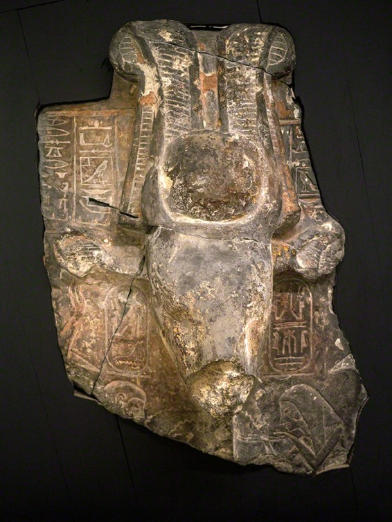A fragment of a statue of a cow's head with a sun disc and two ostrich feathers on her head. What's left of the surrounding area is covered in carved hieroglyphs, including cartouches of Rameses IV