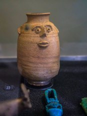 A small, cylindrical ceramic jar with a face molded into the front. The face has protruding nose, lips and ears
