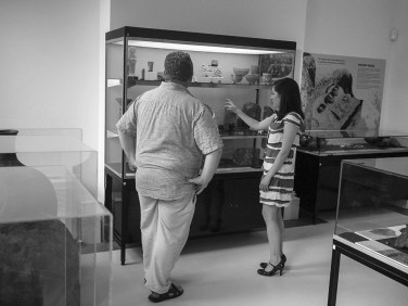 Gina and Roland standing in front of a three-shelved display case