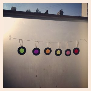 sweet wrapper baubles hanging in a window