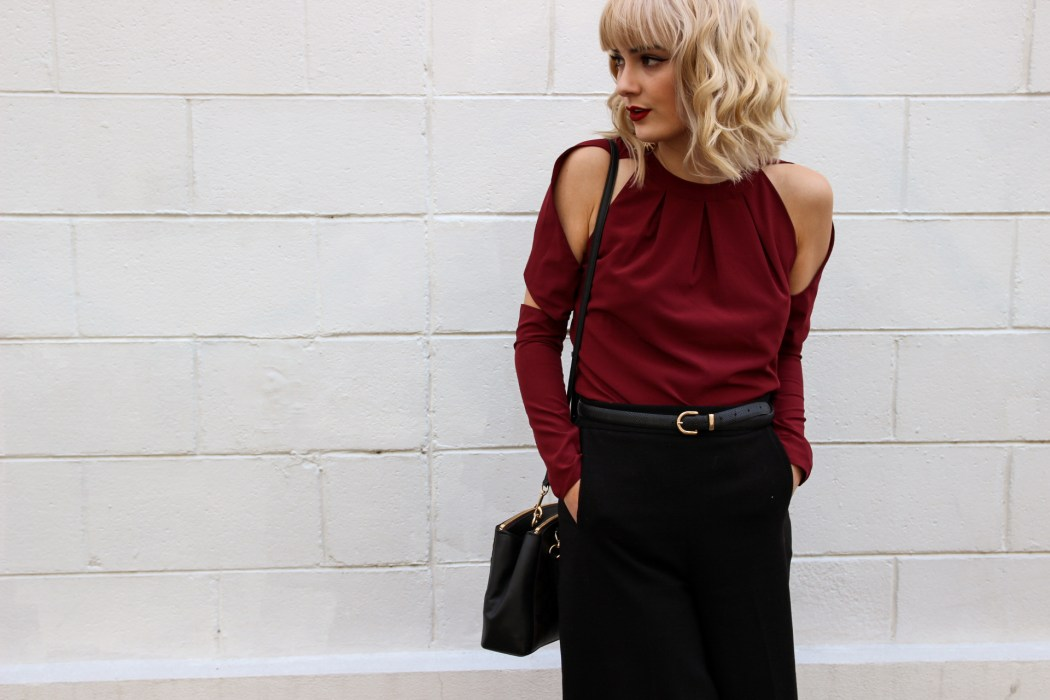 Kristen wears Lucid Label's Twisted Sleeve Top in Maroon.