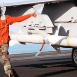 "Aviation Ordnanceman 3rd Class Quentin Bryant, from Augusta, GA, gives a ""thumbs up"" following the inspection of an AGM-88 ""HARM"" air-to-ground high speed missile, loaded on an F/A-18C ""Hornet."""