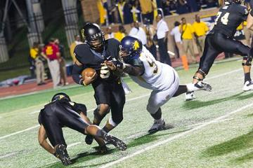 Sophomore quarterback Kameron Bryant brushes off a tackle from an N.C. A&T defender in Saturday night's game. Despite a fourth quarter comeback, the Aggies held off the Mountaineers for a 24-21 win. Photo by Paul Heckert | The Appalachian