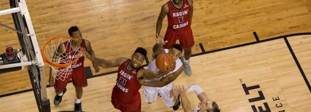 Senior Ragin' Cajun forward Shawn Long splits Moutaineer forwards Griffin Kinney and Jacob Lawson and attempts a dunk, before being blocked by Lawson, during Thursday's game. Louisiana-Lafayette defeated App State 87-76.  Photo by Chris Deverell