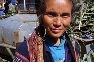 An elderly woman from the Black Hmong tribe selling bracelets on the street