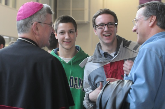 Archbishop Nienstedt visits with Karl Skogan, left, and his sons Elliott, a student at UST and Paul, 16, during the breakfast break. The Skogans are members of St. Jude of the Lake in Mahtomedi. Nearly 1700 men from around the archdiocese gathered at the University of St. Thomas March 16 for the annual Archdiocesan Men's Conference. The event began with a Mass and included presentations from Archbishop John Nienstedt, Raymond de Sousa and Glenn Caruso, UST football coach.