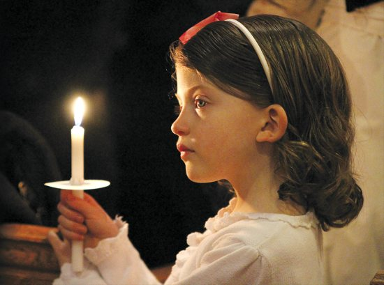 Helena Costanzo of Nativity of Our Lord in St. Paul enjoys Mass by candlelight during the Easter Vigil March 31. She was there with her siblings and parents, Dan and Christine. Turn to page 19 to learn more about the 50-day Easter season. Dave Hrbacek / The Catholic Spirit