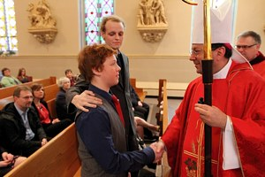 Matthew Brown greets Bishop Lee Piché after being confirmed during a Mass April 22 at St. Mary in Stillwater. His scheduled confirmation was moved up to accommodate the failing health of his sponsor, Zach Sobiech, center. (Dave Hrbacek/The Catholic Spirit)