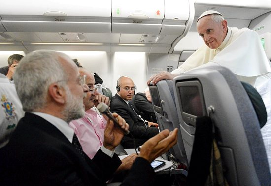 Pope Francis listens to a question from a journalist on his flight heading back to Rome July 29. The pope answered questions from 21 journalists over a period of 80 minutes on his return from Brazil. CNS photo / pool via Reuters