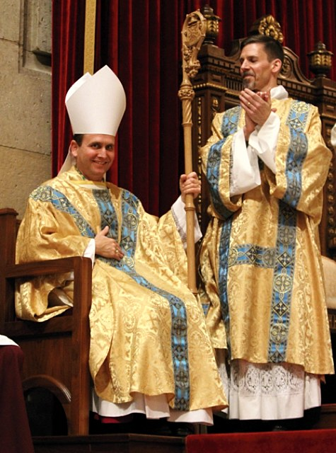 After receiving his crosier and miter, Bishop Cozzens is applauded by the congregation, including Deacon Joseph Michalak, right.