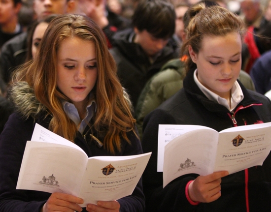 From left, Carolyn Harrington and Rachel Kleszyk, eighth-graders at St. John the Baptist School in New Brighton, sing during the prayer service.