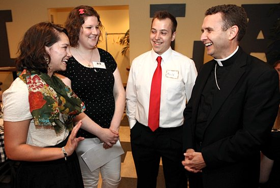 From left, Victoria Ledesma of Holy Family in St. Louis Park, Maddie McCarthy of Holy Family and Nick Haugan of Holy Spirit in St. Paul visit with Bishop Andrew Cozzens May 27 during a Theology on Tap event at Mozza Mia Pizza Pie and Mozzarella Bar in Edina. Bishop Cozzens spent the evening answering questions and visiting with the young adults. McCarthy coordinated the event.  Dave Hrbacek/The Catholic Spirit
