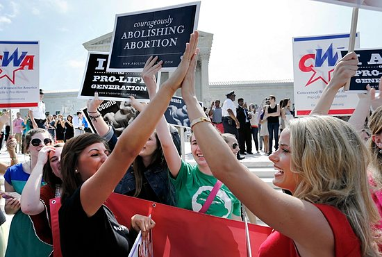 Pro-life demonstrators celebrate June 30 outside the U.S. Supreme Court in Washington as its decision in the Hobby Lobby case is announced. The high court ruled that owners of closely held corporations can object on religious grounds to being forced by the government to provide coverage of contraceptives for their employees. CNS/Jonathan Ernst