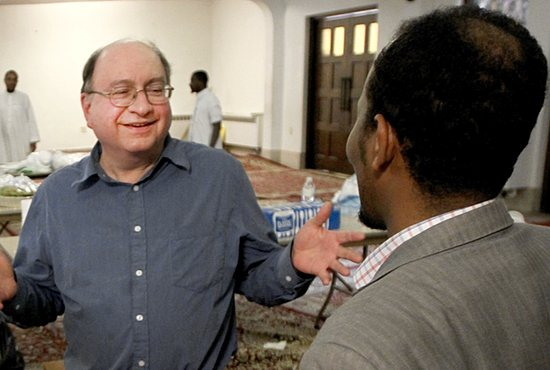 From left, Greg Cosimini talks with Ahmed Diriye inside the former St. John church building in St. Paul June 27. A Muslim group bought the building, which is now called the Darul-Uloom Islamic Center, and had an open house to welcome people in the neighborhood, including former St. John parishioners such as Cosimini.  Dave Hrbacek/The Catholic Spirit