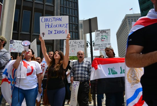 Protesters display signs and carry flags during an Aug. 1 protest in Detroit. CNS photo/Mike Stechschulte, The Michigan Catholic