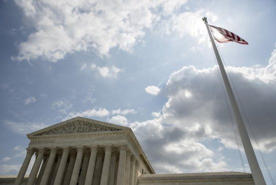 The U.S. flag flies in front of the Supreme Court in Washington in this file photo from May 18, 2015. CNS photo/Joshua Roberts, Reuters