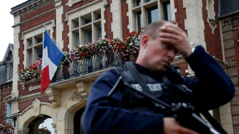 A policeman reacts as he secures a position in front of city hall after two assailants killed 84-year-old Father Jacques Hamel and took five people hostage during a weekday morning Mass  at the church in Saint-Etienne-du-Rouvray, France, near Rouen July 26. (CNS photo | Pascal Rossignol/Reuters)