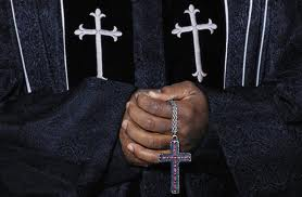 """African American Pastor holding cross"""