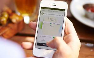 A man uses the Uber app to order a ride