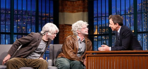 LATE NIGHT WITH SETH MEYERS -- Episode 303 -- Pictured: (l-r) Comedians John Mulaney as George St. Geegland and Nick Kroll as Gil Faizon from the off-broadway play 'Oh, Hello', during an interview with host Seth Meyers on December 16, 2015 -- (Photo by: Lloyd Bishop/NBC/NBCU Photo Bank)