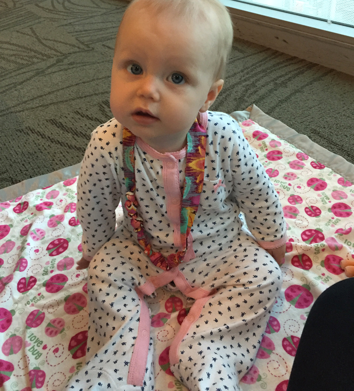 Amelia modeling a fabric covered bead necklace, perfect for teething!