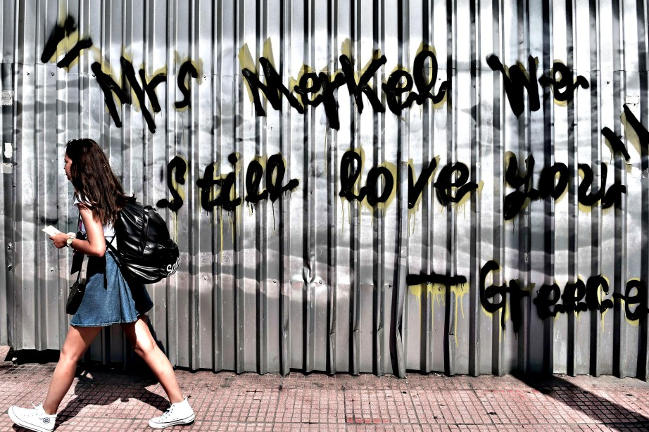 "A young woman walks past a graffiti read...A young woman walks past a graffiti reading ""Mrs Merkel we still love you - Greece"" in central Athens on June 19, 2015. The European Central Bank's decision-making governing council will hold an emergency session on June 19 to discuss a request from the Bank of Greece for an increase in liquidity to Greek banks. AFP PHOTO / ARIS MESSINISARIS MESSINIS/AFP/Getty Images"