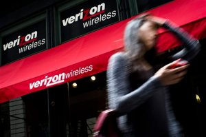 In this Thursday, June 6,  2013, file photo, a pedestrian uses her cell phone as she passes a Verizon Wireless store on Broadway in Lower Manhattan, in New York.  Verizon Communications Inc. reports quarterly financial results before the market opens on Tuesday, Jan. 21, 2014 (AP Photo/John Minchillo, File)