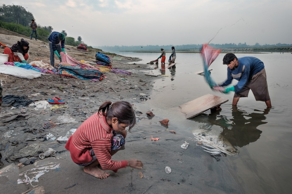 A child draws in the sand of the Yamuna as the dhobis work rinsing the old saris in the background.