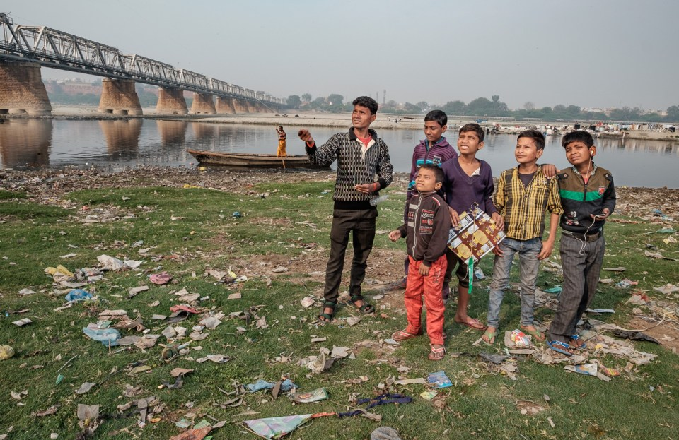 Children play on the banks of the Yamuna flying kites.