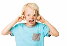Child plugging ears and screaming