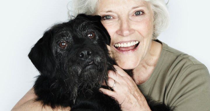 Smiling older woman hugging her black dog