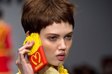 Model Lindsey Wixson holds the Moschino iPhone case on the catwalk at Milan Fashion Week.