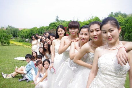 Across China, hundreds of students graduating from college - both men and women - are marking the event not in caps and gowns, but in wedding gowns.