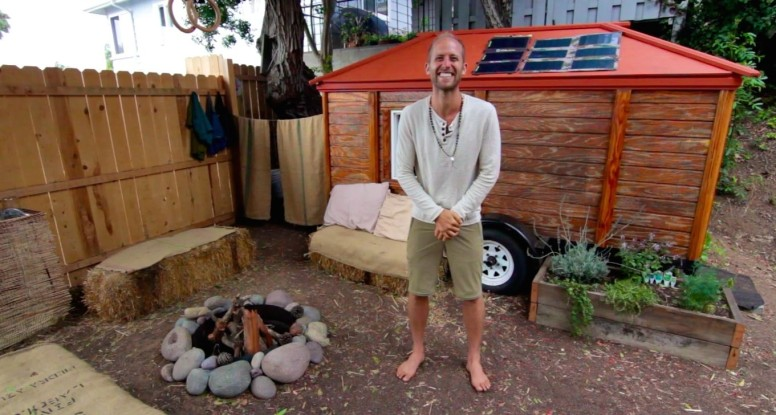 Rob Greenfield next to his off grid tiny house
