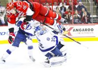 Carolina Hurricane Brandon Sutter (16) airborne over Tampa Bay Lightning goalie Mathieu Garon (Andy Martin Jr)
