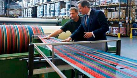 Britain's Prime Minister David Cameron (R), looks at textile machinery during a visit to Camira, a textile factory in Colne Valley, Yorkshire, northern England, April 9, 2015. REUTERS/Kirsty Wigglesworth/Pool