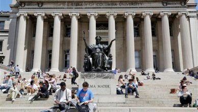 Students sunbathe on the steps of Columbia University's Low Memorial Library next to Daniel Chester French's sculpture, Alma Mater, April 29, 2015 in New York. (AP Photo/Mark Lennihan)