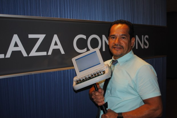 Oscar Garzon holding stenotype machine at Plaza College, Qeens