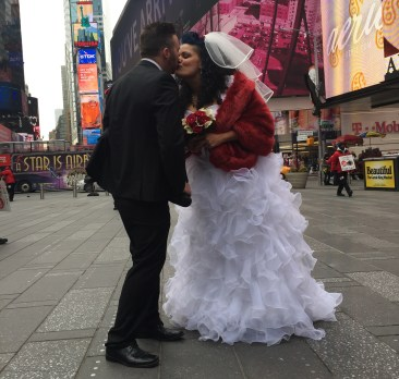 Stephanie Torres and Tim Porter kissing in Times Square before their wedding. (The Ink/Kirsten Watson)
