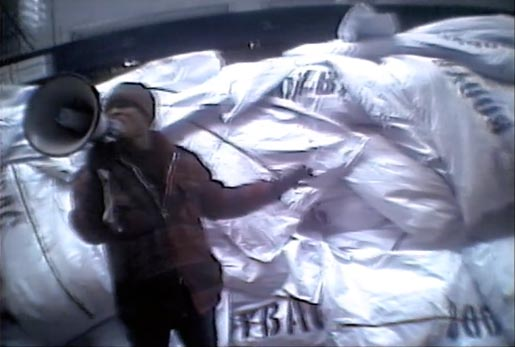 Man with megaphone stands in front of body bags in Truth TV Ad