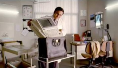 Doctor places large electrocardiograph in a bag